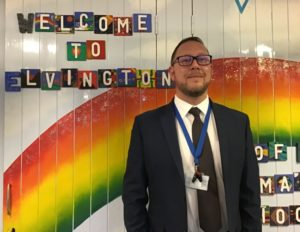 Andrew Buttery standing in front of a display with an image of a rainbow and the text 'welcome to Elvington'