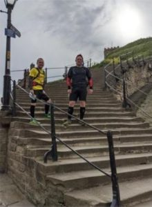 Image of two smiling men, wearing running clothes, standing on the steps up to Whitby Abbey.